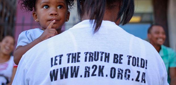 Une femme participant à la campagne Right2Know (« droit de savoir ») manifeste avec son enfant contre le projet de loi sur les informations relatives à l'État, qui permettrait de poursuivre en justice les informateurs, les défenseurs publics et les journalistes qui divulguent la corruption, à Cape Town le 25 avril 2013. (AP/Schalk van Zuydam)