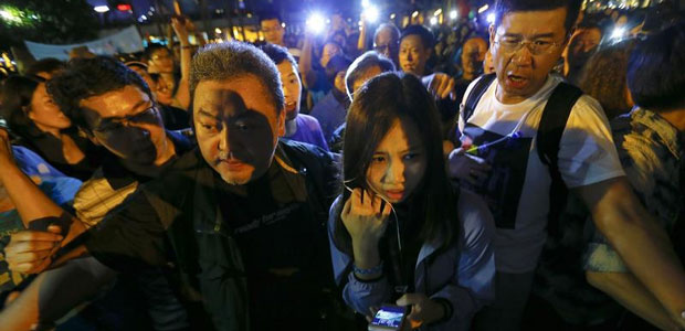 Wong Wing-yin, a reporter for Hong Kong's public broadcaster, RTHK, is escorted to safety during a pro-government protest on October 25, 2014, during which three journalists were assaulted. (Reuters/Damir Sagolj)