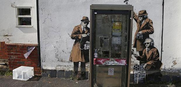 Grafite atribuído ao artista de rua Banksy é visto perto dos escritórios da agência de espionagem da Grã-Bretanha, sede das Comunicações do Governo, ou GCHQ (na sigla em inglês), em Cheltenham, Inglaterra, em 16 de abril de 2014. (Reuters / Eddie Keogh)