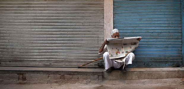 A man reads a newspaper in front of closed shops along the roadside in Delhi, India, on October 10, 2014. (Reuters/Ahmad Masood)