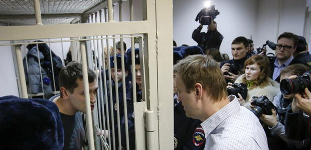 Russian opposition leader and anti-corruption blogger Alexei Navalny, right, talks with his brother and co-defendant Oleg inside a defendants' cage during a court hearing in Moscow on December 30, 2014. (Reuters/Sergei Karpukhin)