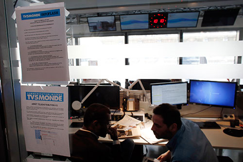 A picture taken on April 9, 2015, shows a note on the window of a newsroom at French television network TV5Monde headquarters in Paris, after TV5Monde was hacked by individuals claiming to belong to the Islamic State group. (AFP/Thomas Samson)