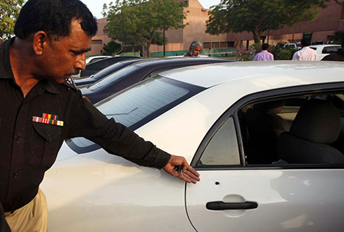 A police official points to bullet holes in Hamid Mir's car following the attack on him in April 2014. (Reuters/Athar Hussain)