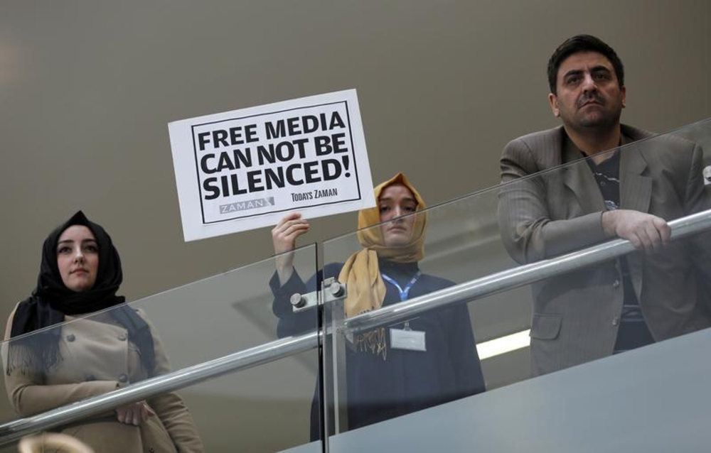 A journalist holds a placard at the headquarters of Zaman daily newspaper in Istanbul on December 14, 2014. Turkish police raided media outlets close to U.S.-based Muslim cleric Fethullah Gulen, including Zaman, and detained 23 people. (Reuters/Murad Sezer)