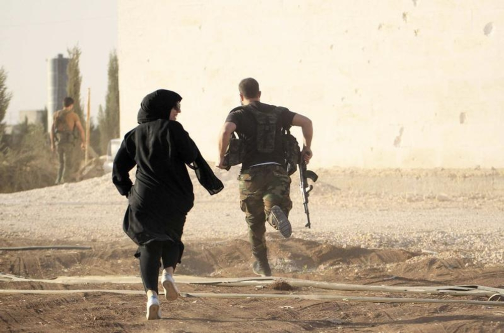 A female reporter runs with a rebel fighter while evading snipers near Aleppo, Syria, October 10, 2014.