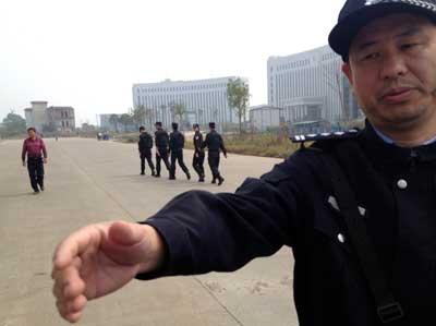 In this October 28, 2013, photo, a Chinese police officer reaches toward a journalist outside the courthouse where activists are on trial in Xinyu city, Jiangxi province. (AP/Aritz Parra)