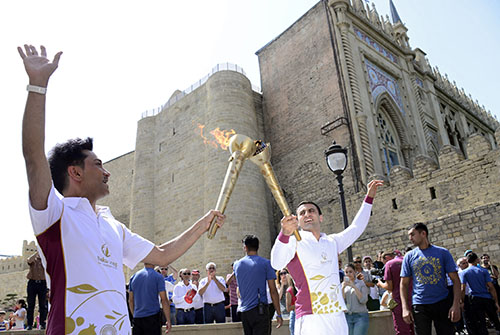 Azerbaijani singer Faig Agayev, left, and wrestler Farid Mansurov take part in the Baku Games torch relay on June 9. Azerbaijan has cracked down on the press in the lead up to the first European Games. (AFP/Tofik Babayev)