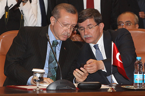 Recep Tayyip Erdoğan, left, looks at a cell phone during a meeting in 2013. Since Erdoğan became president there has been an increase in insult charges filed against Turkey's press. (AP/Abdeljalil Bounhar)