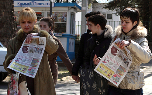 Распространяемые в Севастополе газеты с изображением российского паспорта на первой полосе. Жителям Крыма был дан один месяц на уведомление российских властей о том, что они хотят сохранить гражданство Украины . (AFP/Юрий Лашов)