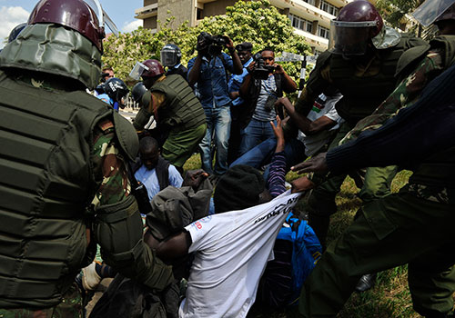 Police arrest a protester at a rally against proposed security laws which threaten fines and jail over reports deemed to 'undermine terror investigations.' (AFP/Simon Maina)