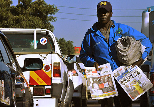 Newspapers reporting on the ICC dropping charges against President Kenyatta are sold in a Nairobi street in 2014. Journalists working outside the city are more vulnerable to attacks and harassment. (AFP/Simon Maina)