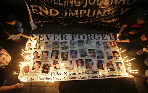 Philippine citizens light candles in memory of the 2009 Maguindanao massacre. No one has been convicted in the case, and one of the alleged masterminds died of a heart attack earlier this month. (AP Photo/Aaron Favila)
