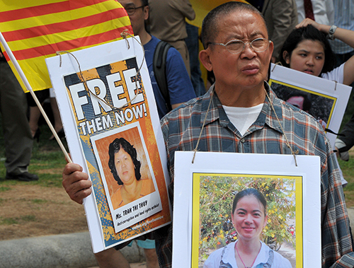 Pictures of Vietnamese political prisoners are waved at a rally outside the White House in July to protest Trong's visit with President Obama. (AFP/Mladen Antonov)