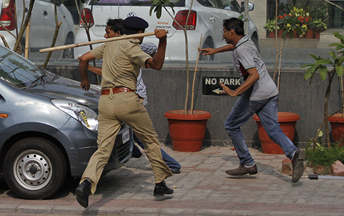 A policeman uses a baton to disperse protesters in Gujarat on August 25. Journalists were among those injured as police broke up the crowds. (AP/Ajit Solanki)