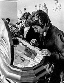 Margarita Patiño, Bustíos' widow, looks in his coffin during his wake. (Caretas)