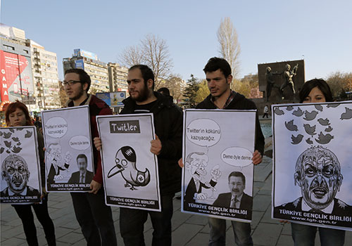 Cartoons of Turkey's attempt to silence critics by blocking Twitter are held up by protesters. Turkey will need to improve its press freedom record before being admitted into the EU. (AP/Burnhan Ozbilici)