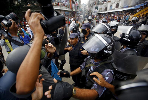 Police try to prevent journalists from covering clashes between police and protesters demonstrating against the draft of a new constitution in August 15. (Reuters/Navesh Chitrakar)