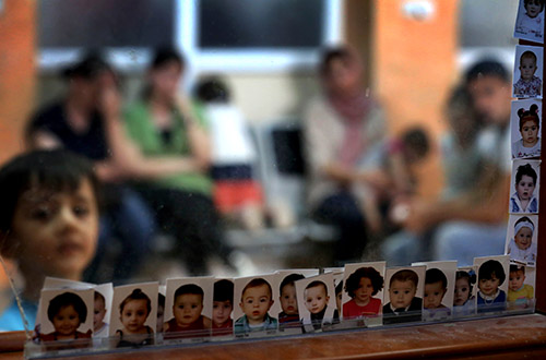 Photos of children who lost their documents while fleeing militants in Mosul are displayed at an Iraqi passport office. Many journalists fled the violence but the fate of those who remained is hard to determine. (AFP/Safin Hamed)