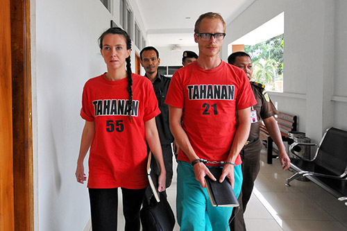 Neil Bonner and Rebecca Prosser are escorted into court in Indonesia on October 22. The British filmmakers are on trial for working without a journalist visa. (AFP/Iklil Faiz)