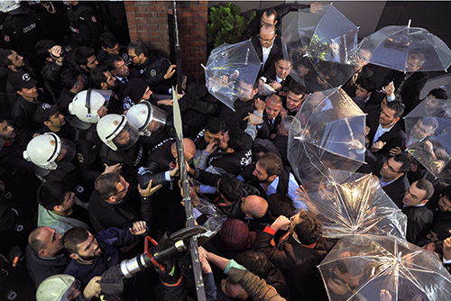 Riot police force their way into the headquarters of an opposition news outlet on October 28 as Turkey forces the Koza İpek Group to replace senior managers with a government-approved board of trustees. (AP/Usame Ari, Cihan News Agency)