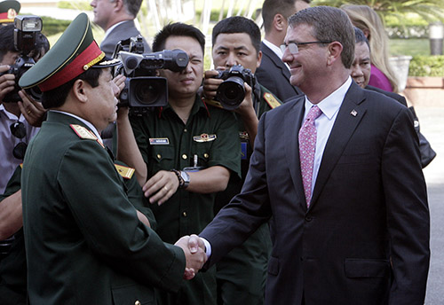 Defense minister General Phung Quang Thanh shakes hands with his U.S. counterpart, Ashton Carter, in June. Thanh says Vietnam's human rights record should not influence the U.S. ban on weapons sales. (AP/Tran Van Minh.)