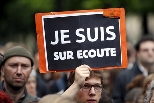 A protester holds a placard which reads 'I know they tap my phones' during a rally against the proposed surveillance bill in France. (Reuters/Charles Platiau)