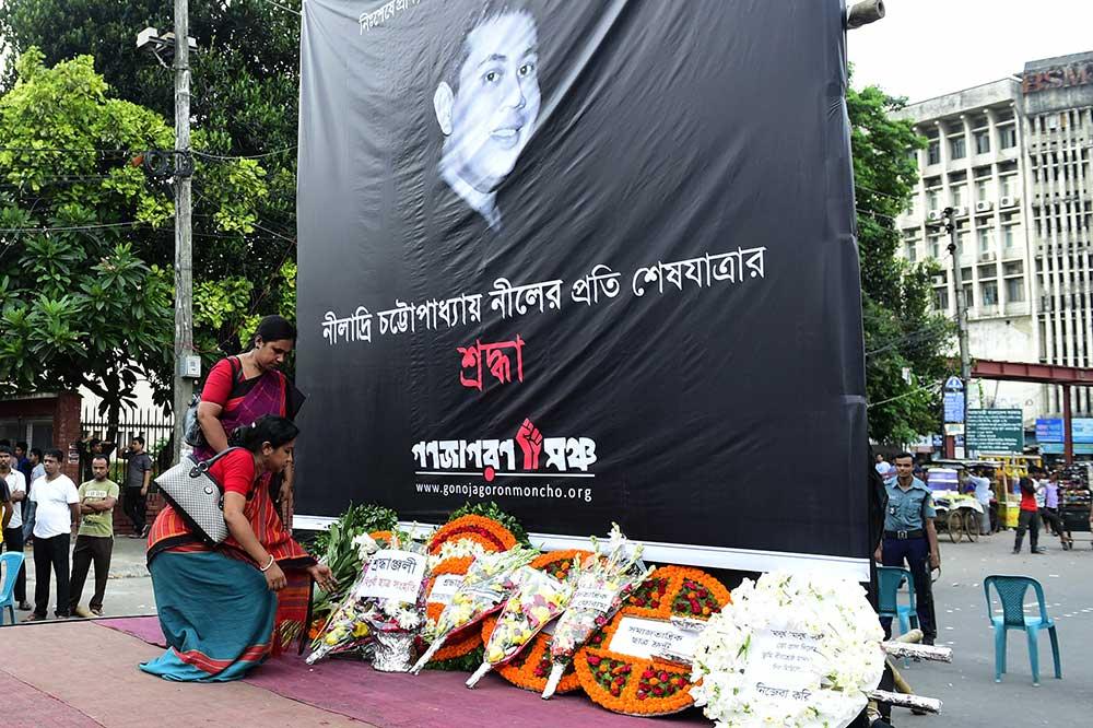 Ofrendas florales colocadas bajo un cartel con la imagen de Niloy Neel en agosto. Neel es el cuarto bloguero que ha sido asesinado con machetes por extremistas en Bangladesh en 2015. (AFP/ Munir uz Zaman)