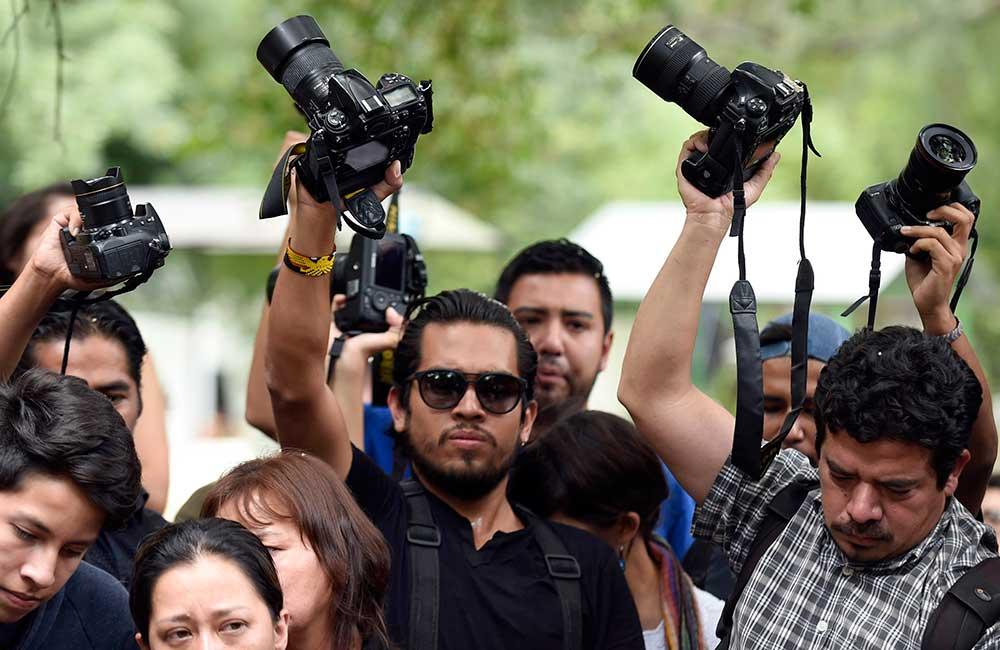 Друзья и коллеги Рубена Эспинозы стоят с поднятыми над головой фотоаппаратами на похоронах фотожурналиста в Мексике. Рейтинг безнаказанности в стране почти удвоился с 2008 года. (AFP/Alfredo Estrella