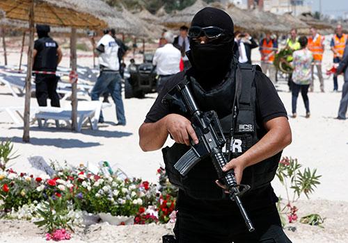 شرطي يحرس شاطئ في تونس حيث فتح مسلحٌ النارَ على سواح في يونيو/حزيران. وقد تعرضت وسائل الإعلام لضغوط من السلطات ومن الجماعات المتطرفة منذ وقوع هذا الاعتداء الإرهابي. (أسوشيتد برس/عبد الجليل بونهار)