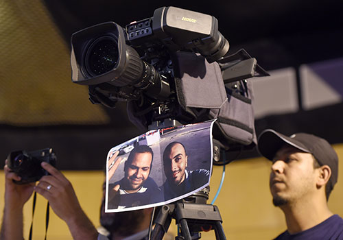 An image of Sofiene Chourabi and Nadhir Guetari hangs from a camera in May. The Tunisian government is accused of being opaque about the case of the journalists, who Islamic State claims to have killed in Libya. (AFP/Fethi Belaid)