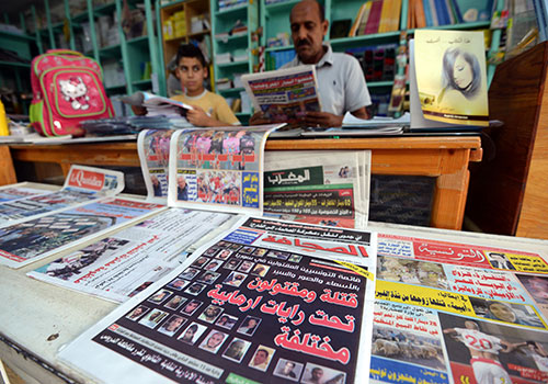 Copies of pro-government daily Essahafa, showing the faces of suspected Tunisian jihadists killed fighting for extremist groups in Syria, are sold at a kiosk in Tunis. (AFP/Fethu Belaid)