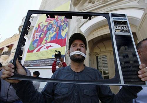 صحفي يحمل إطار جهاز تلفزيون خلال احتجاج جرى في عام 2012. تعرضت وسائل الإعلام التونسية لضغوط في عام 2015. (رويترز/أنيس معلي)