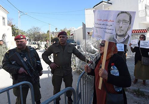 متظاهرون أمام محكمة عسكرية في تونس يطالبون بالإفراج عن المدون ياسين العياري. وقد أفرج عنه قبل انتهاء مدة محكوميته، وذلك في أعقاب مطالبات دولية بالإفراج عنه. (وكالة الأنباء الفرنسية/فتحي بلعيد)