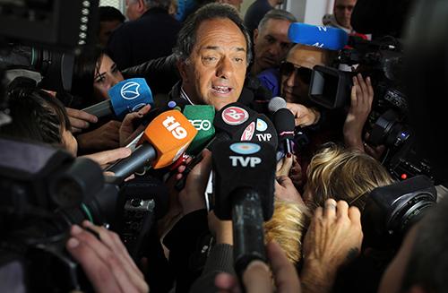 El caniddato presidencial Daniel Scioli es rodeado por la prensa el día de las elecciones presidenciales. Un canal de cable progubernamental lo declaró errónamente ganador a pesar de que los resultados determinaron una segunda vuelta para fines de noviembre. AP/Enric Marti)