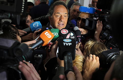 Presidential candidate Daniel Scioli is surrounded by press on election day. A pro-government TV station erroneously declared him the winner despite the vote going to a runoff in late November. (AP/Enric Marti)