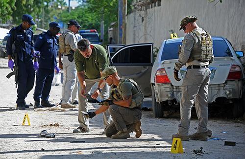Security officers investigate after a car bomb killed Somali journalist Hindia Haji Mohamed. (AFP/Mohamed Abdiwahab)
