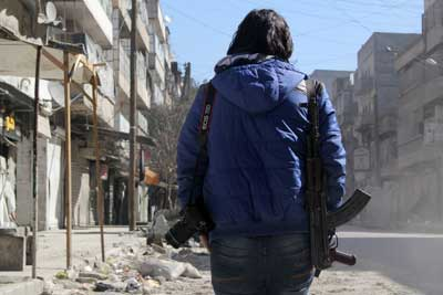A young Syrian journalist carries a camera and a gun on February 9, 2014, in Aleppo. (AFP/Aleppo Media Center/Mohammed Wesam)