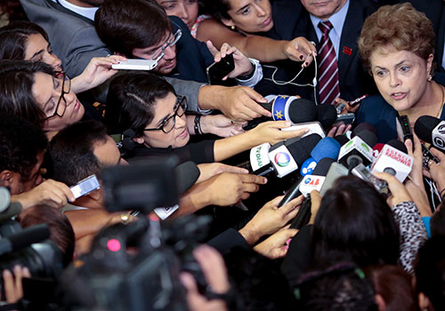 La presidenta brasileña, Dilma Rousseff, rodeada por periodistas. Las autoridades brasileñas obtuvieron avances en la lucha contra la impunidad al lograr varias condenas recientemente, pero al menos seis periodistas cayeron en cumplimiento de su labor en 2015, una cifra sin precedentes. (AFP/Wenderson Araujo)