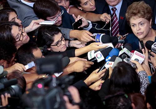 الرئيسة البرازيلية ديلما روسيف يحيط بها صحفيون. وقد حققت السلطات البرازيلية إنجازات في مكافحة الإفلات من العقاب إذ أصدرت أحكام إدانة مرتبطة بجرائم قتل استهدفت صحفيين. ولكن لقي ستة صحفيين حتفهم في عام 2015، وهو عدد غير مسبوق في هذا البلد. (وكالة الأنباء الفرنسية/وينديرسون أروهو)