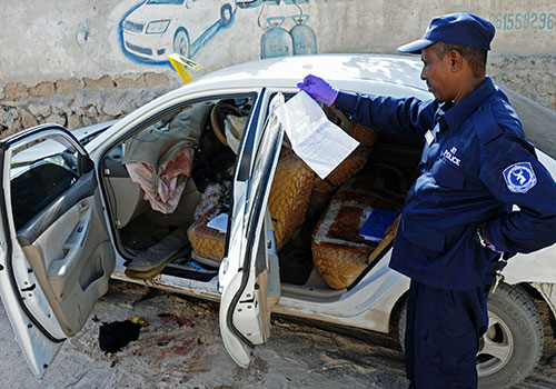 Um oficial de segurança investiga o assassinato da jornalista somali Hindia Haji Mohamed, que foi morta por um carro-bomba em dezembro. (AFP / Mohamed Abdiwahab)