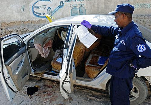 ضابط أمن يحقق في جريمة قتل الصحفية الصومالية هندية حاج محمود، والتي قتلت بتفجير قنبلة في سياراتها. (وكالة الأنباء الفرنسية/ محمد عبد الوهاب)