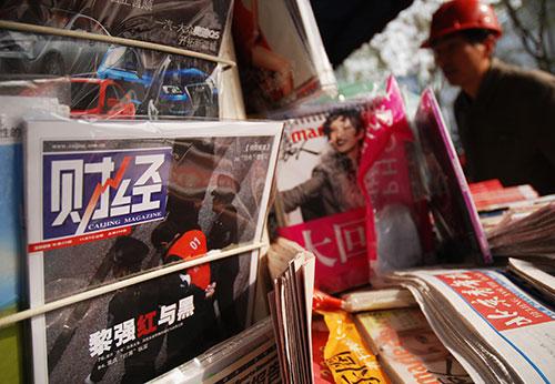 نسخ من المجلة الصينية 'كايجنغ' في كشك لبيع الصحف في بيجين. وفي أغسطس/آب 2015، اعتقلت السلطات الصينية الصحفي وانغ شياولو الذي يعمل في هذه المجلة بتهمة نشر تغطية صحفية 'غير مسؤولة' حول سوق الأسهم.  (وكالة الأنباء الفرنسية/ وانغ زاو)