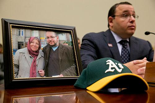 Ali Rezaian sentado junto a una foto que muestra a su hermano, el periodista del Washington Post Jason Rezaian, y a la madre de ambos, durante una audiencia de la Comisión de Relaciones Exteriores de la Cámara de Representantes para personas con familiares encarcelados en Irán. (AP/Jacquelyn Martin)