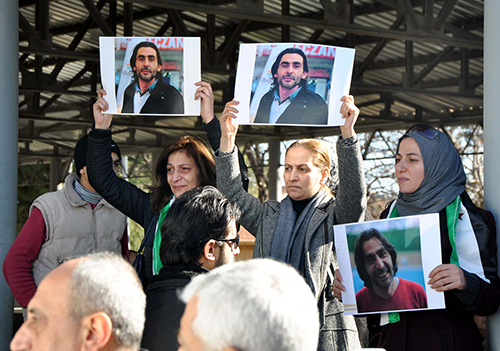 Pictures of filmmaker Naji Jerf are held up at his funeral in Gaziantep in December. Syrian media activists based in Turkey say the murder of Jerf and two other journalists makes the country feels less secure. (STR/AFP)