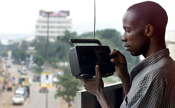 A man listens to the news on the radio in Kampala, August 16, 2003 (Reuters).