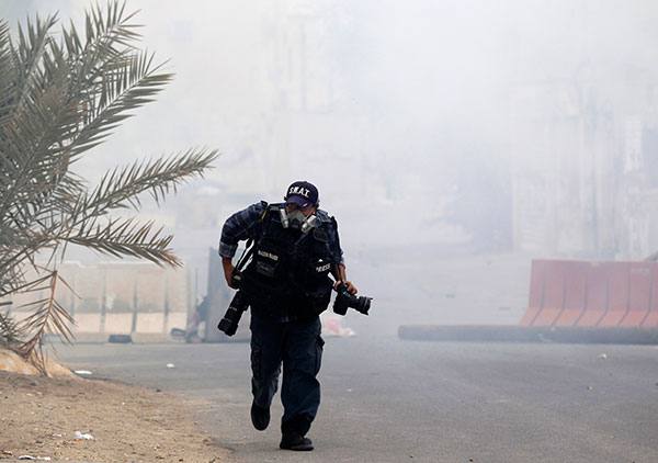 A photojournalist runs from tear gas at an anti-government protest in Bahrain, March 24, 2012. (Reuters/Ahmed Jadallah)
