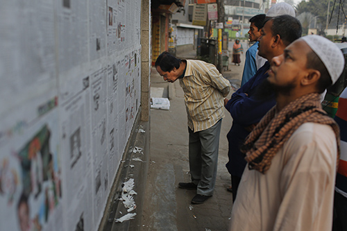 Bangladeshis read a newspaper pasted to a wall in Dhaka. The editor of The Daily Star, based in the city, is facing multiple legal cases after saying he published unsubstantiated reports several years ago. (AP/A.M. Ahad)