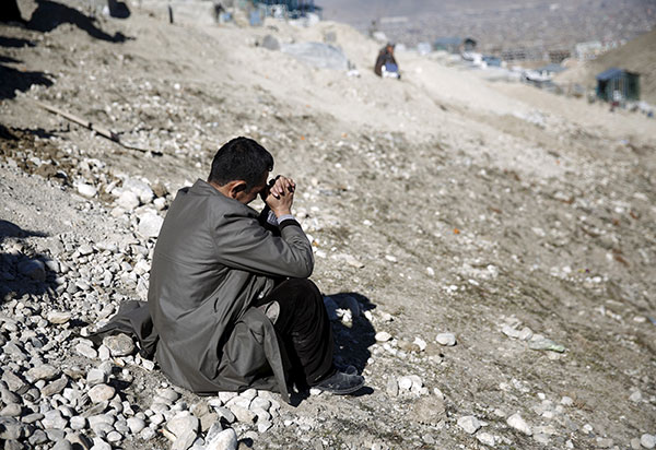 The brother of a Tolo TV employee killed in a suicide attack on Kabul television station weeps at his funeral, January 26, 2016 (Reuters/Ahmad Masood).