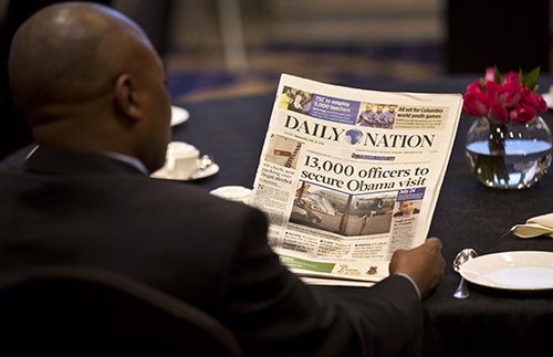 A man reads a copy of Kenyan daily, the Nation. Gado, whose political cartoons were regularly featured in it, says his contract with the paper was terminated. (AP/Ben Curtis)