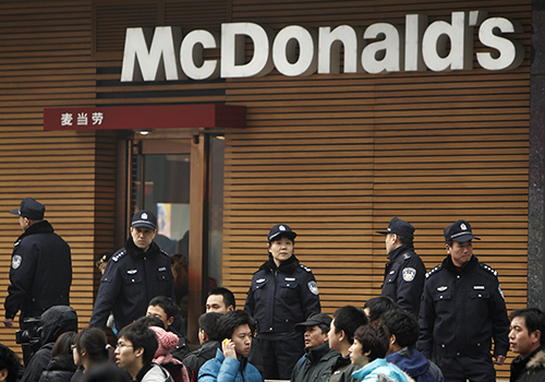 Police stand guard outside a McDonald's restaurant in Beijing in 2011. Weibo's censors were ordered to look out for posts on 'McDonald's' and 'Combo No.3' which were used as code words to plan protests in 2011. (AP Photo/Andy Wong)